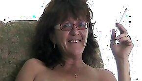 Older granny is smoking a cigarette naked